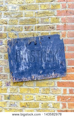 Close-up of blue painted wooden board hanging on colorful red and yellow brickwall.