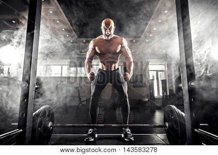 Athlete motivates screaming before barbells exercise at gym. Smoke