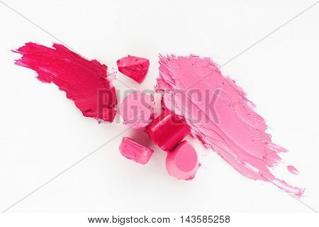 Pink lipstick texture, damaged cosmetic, flat lay. Top view on rosy lip gloss slices and smear on white background. Variety of rose shades of rouge. Femininity, makeup, beauty concept