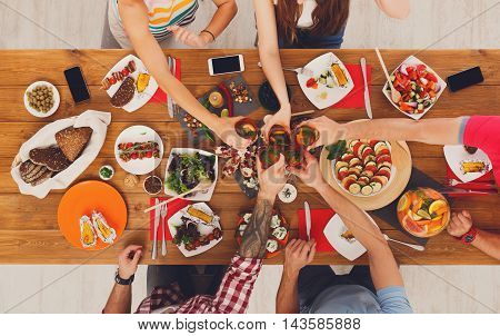 People clink glasses, saying cheers, eat healthy meals at party dinner table. Friends celebrate with organic food, ratatoille and corn barbecue on wooden table top view.
