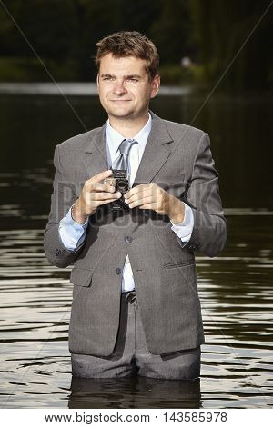 Crazy businessman in suit deep in water