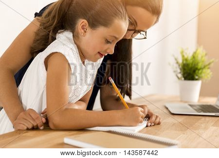 Mother and daugther at home doing homework together