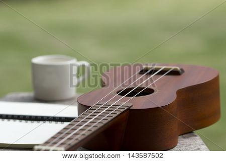 blurred ukulele on green background with cup of coffee and notepad