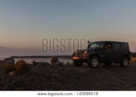 Leningrad oblast , the Karelian isthmus, Russia , August 21, 2016 , Jeep on the shore of Ladoga lake, the Jeep Wrangler is a compact four wheel drive off road and sport utility vehicle