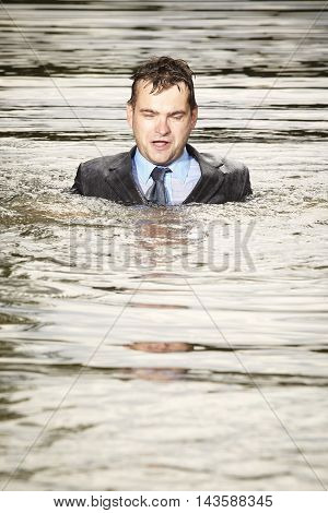 Crazy businessman in suit and tie swimming in water