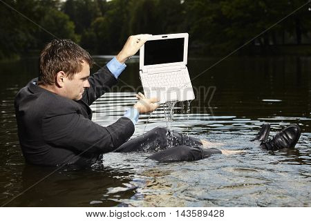 Crazy businessman in suit has a water in notebook