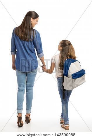 Mother and her little daughter walking together going to the school