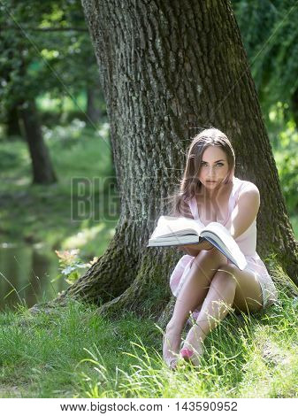 Pretty Woman Reading Book On Grass