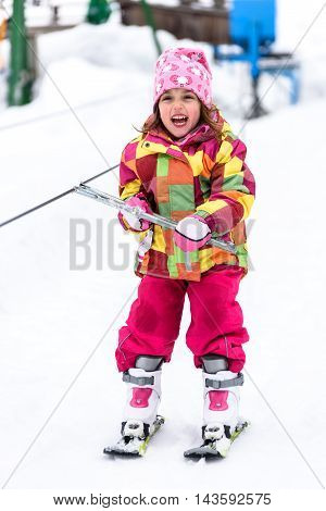 Little girl is learning to ski in ski resort. Child is using ski baby lift conveyor skiing for the first time. Active children are happy.