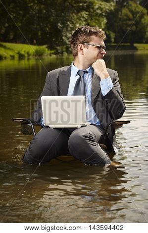 Crazy businessman in suit relaxing on chair in summer water