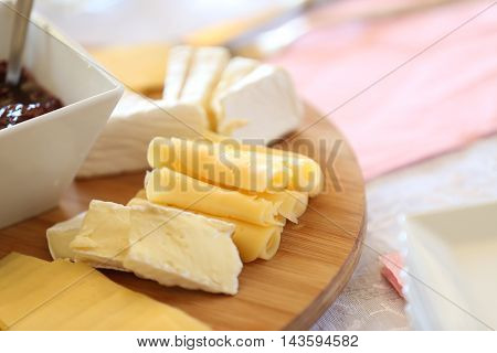 cheese platter with cherry preserves, grapes and various cheeses on a wooden board