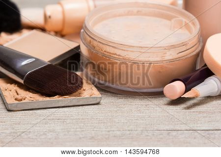 Close-up of various makeup products and accessories to even out skin tone and complexion. Concealers, foundation, powder on shabby wooden surface. Side view, shallow depth of field