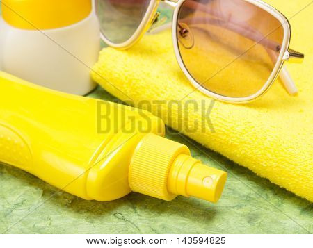 Sunscreen spray bottle, jar of sun cream, towel and sunglasses. Sun protection cosmetic products. Close-up, very shallow depth of field
