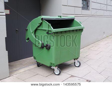 Emptied garbage bin on a street. Waste theme.