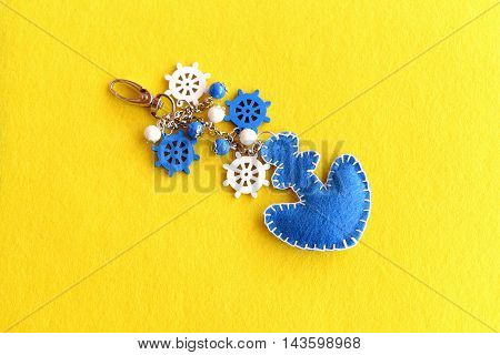 Felt anchor keychain decorated with beads and wooden ship wheels. Handmade charm keychain for car or beach bag isolated on yellow felt background. Summer crafts idea