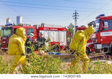 CZECH REPUBLIC, DOBRANY, 4 JUNE, 2014: Mans in protective hazmat suit and fire trucks