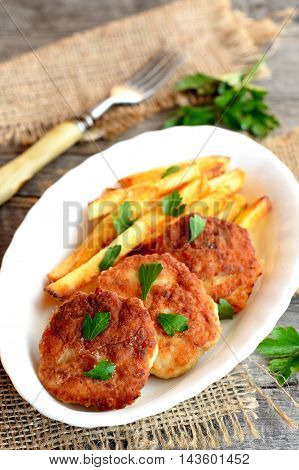 Fried meat cutlets served with fried potatoes. Turkey fillet cutlets with potatoes on the plate. Fork, sprig of fresh parsley on an old wooden background. Lunch or dinner menu. Closeup