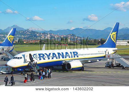 BERGAMO, ITALY - APRIL 25, 2016: Passengers boarding Ryanair aircraft at Orio Al Serio international airport with view of Bergamo and Alps