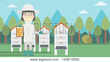 An asian female farmer wearing protective suit. Bee-keeper holding a framework in hand and showing thumb up on the background of apiary. Vector flat design illustration. Horizontal layout.