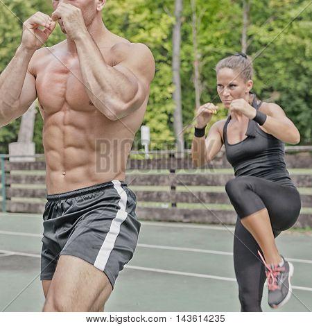 Instructor and female athlete on tae bo training outdoors