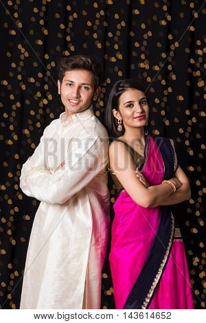 portrait of cheerful young indian couple in traditional wear in diwali