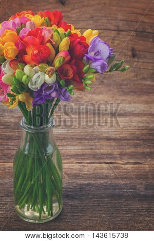 Fresh freesia flowers in glass bottle on wooden table background, retro toned