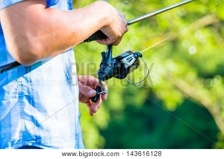Close shot of sport fisherman reeling in the line on his fishing rod