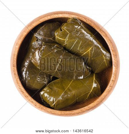 Dolma, stuffed vine leaves in a bowl on white background. Sarma in Turkish or Dolmades in Greek cuisine. Stuffed with meat or meatless with rice. Isolated macro food photo and close up from above.
