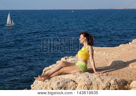 pretty girl sits on a cliff and looking at the sea