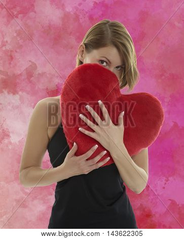 Young beautiful woman hiding behind a red heart shaped pillow with a red aquarell painted background