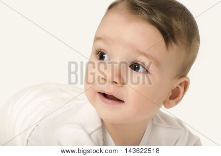 Cute baby boy looking to the side. Adorable baby crawling looking curious isolated on white. Baby lying on his tummy.