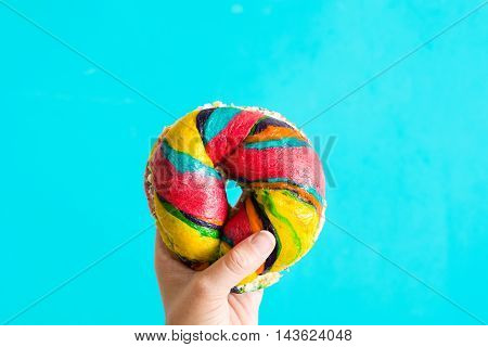 Colorful bagel with cheese and sprinkles in hand on blue background