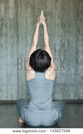 Young woman practicing yoga on a background of gray concrete wall. Urban background. Monochrome image.