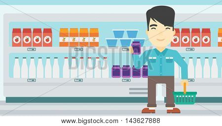 An asian young man holding shopping basket in one hand and milk product in the other. Male customer shopping at supermarket with basket. Vector flat design illustration. Horizontal layout.