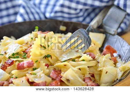 Pasta with fried white cabbage and bacon, an Austrian specialty called 'Krautfleckerl', served in an iron frying pan
