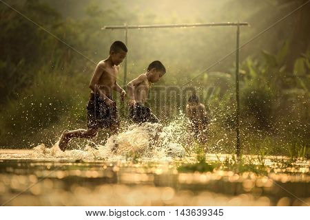 Three boys playing football in the brook at NongkhaiThailand.