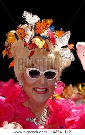 New York City - April 20 2014: Duchess Doris Dear sporting shades a frilly wrap and a butterly bonnet at the Easter Parade on Fifth Avenue