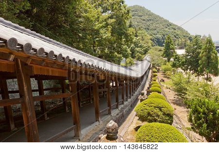 OKAYAMA JAPAN - JULY 20 2016: The 400 meter long covered walkway at Kibitsu Shinto Shrine in Okayama Prefecture. Kibitsu Shrine was the chief Shinto shrine (ichinomiya) of Bitchu Province