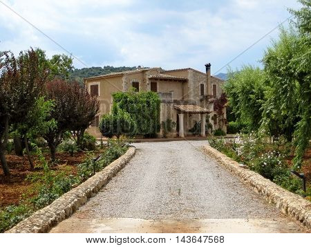 Pollenca Majorca Spain - June 28 2008: Finca vacation rental home - view from public street outside of the property - gate opened - driveway with garden in front