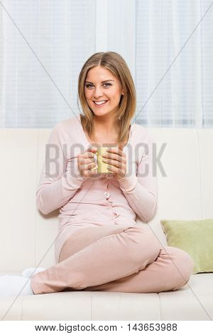 Young beautiful woman drinking coffee or tea and enjoys in her free time.