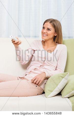 Beautiful woman sitting on sofa and watching tv.