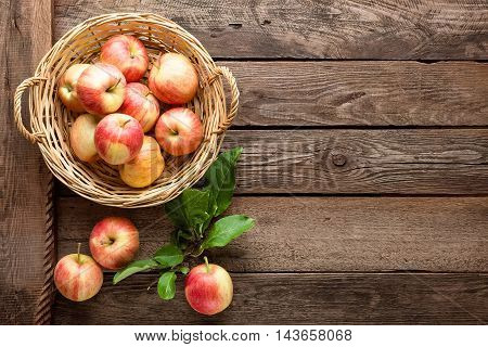 fresh red apples in wicker basket on wooden table