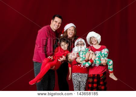 A large young family poses for a Christmas portrait on red. The youngest kids are being held and the oldest sister is laughing while the middle sister wears a Santa hat and beard.