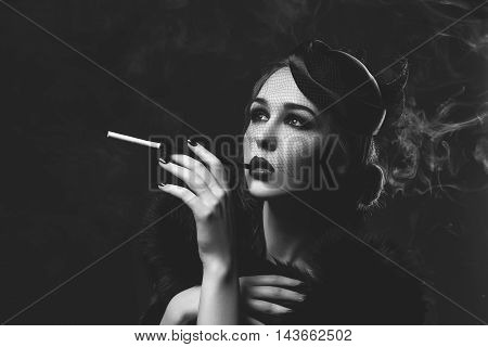 Beautiful young woman with smoky eyes and full red lips holding cigarette holder. Vintage head piece. Retro styling. Studio beauty shot over smoky background. Copy space. Monochrome.