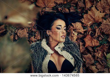 Closeup of young women lying in fallen leaves