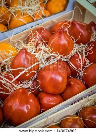 Fresh red ripe tomatoes in wooden baskets on sale on a farmers Borough Market in London