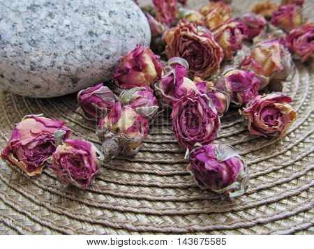 Closeup of dried tea roses buds with stone on wicker rug background
