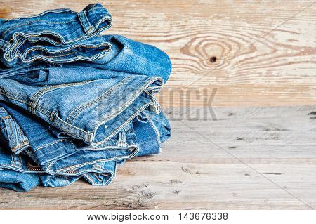 jeans stacked on a wooden background with copy cpase
