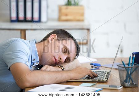 Young Man Sleeping On Office Desk