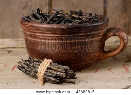 Wellness Tea drink, Bitter Twisted Leaves of Ilex Kudingcha. Green tea Kuding in a clay bowl